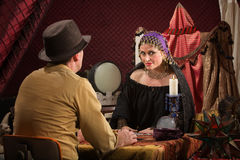 Customer with Fortune Teller. Smiling beautiful fortune teller with crystal ball and customer stock images