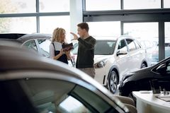 Customer gesturing while discussing with saleswoman. Male customer gesturing while discussing with saleswoman in car showroom Stock Photo