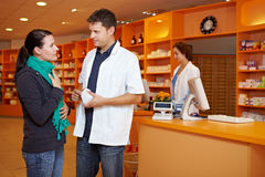 Customer gets advice in pharmacy. Female customer with cold gets advice from pharmacist in pharmacy Stock Photography