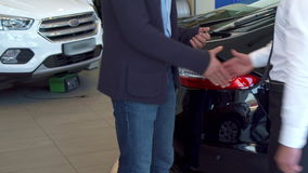 Customer gets car key at the dealership. Customer getting car key at the dealership. Close up of male hands shaking against background of new cars. Two men stock video