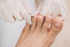 Customer getting toe nails clipped Royalty Free Stock Images