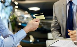 Customer giving credit card to car dealer in salon Royalty Free Stock Image