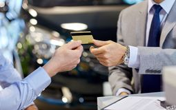 Customer giving credit card to car dealer in salon. Auto business, sale and people concept - close up of customer giving credit card to car dealer in auto show Royalty Free Stock Photography