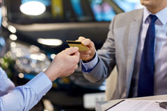 Customer giving credit card to car dealer in salon Royalty Free Stock Photo