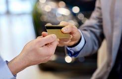 Customer giving credit card to car dealer in salon Stock Photos