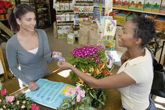 Customer Giving Credit Card To Woman. African American female customer giving credit card to women in gardening store Stock Photography