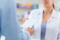 Customer giving prescription to pharmacist Royalty Free Stock Images