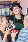 Customer giving waitress coupon on smart phone Royalty Free Stock Photos