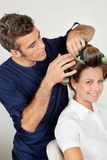Customer With Hairstylist Curling Hair At Parlor Stock Photo