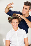 Customer With Hairstylist Setting Curls With. Portrait of female customer with hairstylist setting curls with hairspray in salon stock photos