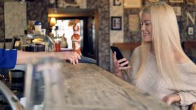 Attractive female at cafe making online payment using smartphone. 4K. Customer hand making online payment using smartphone stock video footage