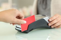 Customer hand passing credit card through the reader Royalty Free Stock Images