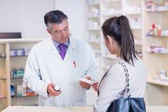 Customer handing a prescription to a pharmacist Stock Photography