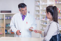 Customer handing a prescription to a pharmacist Royalty Free Stock Photo