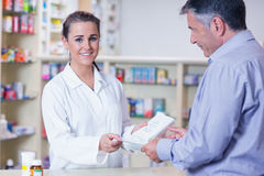 Customer handing a prescription to a smiling trainee Stock Photos