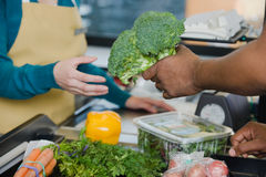 Customer handing a sales assistant broccoli Stock Photo