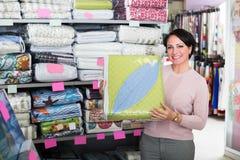 Customer handles bedspread near textiles. Mature woman customer handles bedspread near textiles shelves inside Stock Photography