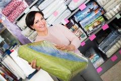 Customer handles bedspread near textiles. Positive customer handles bedspread near textiles shelves inside Royalty Free Stock Image