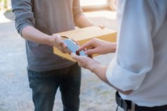 Customer hands appending signature in mobile phone, man receiving parcel post box from courier with delivery service man, express. Delivery, online shopping stock images