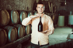 Customer holding bottle of wine. Satisfied customer holding bottle of red wine from wooden barrels Royalty Free Stock Images