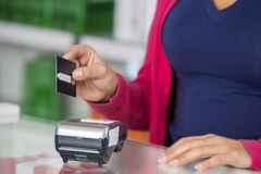 Customer Holding Credit Card Over Reader In Pharmacy. Midsection of female customer holding credit card over reader at counter in pharmacy Royalty Free Stock Images