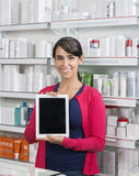 Customer Holding Digital Tablet With Blank Screen In Pharmacy. Portrait of female customer holding digital tablet with blank screen in pharmacy Stock Photography