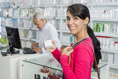 Customer Holding Medicine Box While Chemist Working In Pharmacy Royalty Free Stock Photography