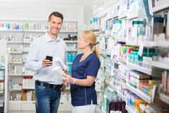 Customer Holding Mobile Phone While Chemist Stock Photos