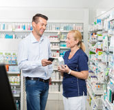Customer Holding Mobile Phone While Pharmacist Stock Images