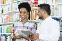 Customer Holding Product While Standing By Chemist Stock Photography
