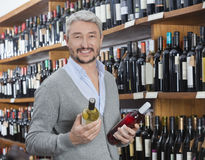 Customer Holding Red And White Wine Bottles In Store. Portrait of happy mature customer holding red and white wine bottles in store Royalty Free Stock Image