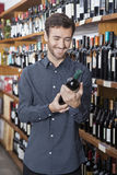 Customer Holding Wine Bottle In Store. Smiling young male customer holding wine bottle in store Royalty Free Stock Image
