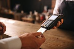 Customer doing payment credit card in cafe. Customer inserting his credit card in the machine to payment at cafe. Customer paying for their order with a credit royalty free stock photo