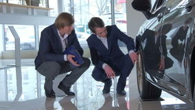 Customer inspecting car wheels. In dealership. Seller and buyer having conversation near the wheel of the car. Young man and salesman examining wheels of the stock video