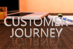 Customer Journey. Letters on wooden desk with laptop computer and a notebook. 3d render illustration Stock Image