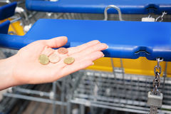 Customer Lacking The Right Coin Needed For A Shopping Cart. A female customer is lacking the right coin needed to get a shopping cart Royalty Free Stock Images