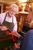 Customer Leaving Violin For Repair In Shop Royalty Free Stock Photos