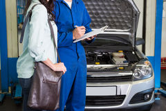 Customer listening to his mechanic Stock Photography