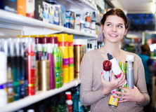Customer looking for hair care products. Smiling young female customer looking for hair care products in cosmetics shop stock photography