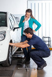 Customer Looking At Mechanic Changing Tire Stock Images