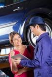 Customer Looking At Mechanic Holding Digital Tablet. Happy female customer looking at mechanic holding digital tablet in garage Stock Photo