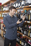 Customer Looking At Wine Bottle In Store. Smiling young male customer looking at wine bottle in store Royalty Free Stock Image