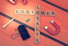 Customer Loyalty theme with smart phone on wooden table.  royalty free stock photography