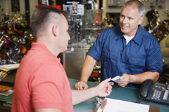 Customer Making Payment In Motorcycle Shop Stock Images