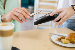 Customer making payment through smartphone. In restaurant Stock Photo