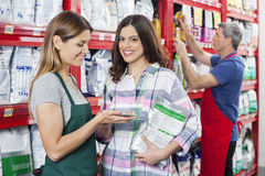 Customer Making Payment To Saleswoman In Pet Shop. Portrait of female customer making payment to saleswoman in pet shop stock photos