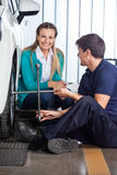 Customer With Mechanic Fixing Tire At Garage. Portrait of happy female customer with mechanic fixing tire at garage Stock Photography