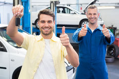 Customer and mechanic smiling at camera Royalty Free Stock Photography