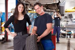 Customer with Mechanic and Tire. A mechanic showing a tire to a happy female customer Stock Photography