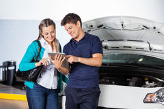 Customer And Mechanic Using Digital Tablet By Car. Female customer and mechanic using digital tablet by damaged car in garage Royalty Free Stock Photography